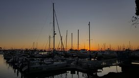 Segelbåtar som tjudras på Marina Dock på solnedgången i San Diego California royaltyfria bilder