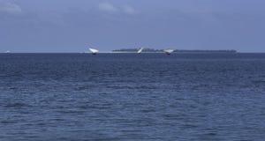 Segelbåtar vid horisonten långt borta fotografering för bildbyråer