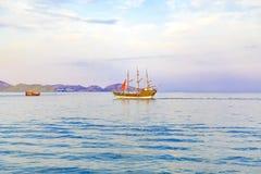 Segelbåten med scharlakansrött seglar på havet går till kusten arkivfoto