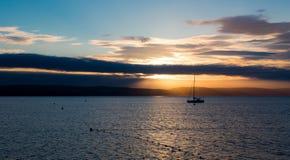 Segelbåten med stupat seglar i soluppgångljus på det fulla havet Royaltyfria Bilder