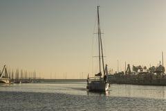 Segelbåten som skriver in en kanal till skeppsdockaporten på hamnen, solnedgångsolljus, skiner Fotografering för Bildbyråer