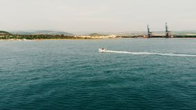 Segelbåten svävar längs kustlinjen i dagsljuset stock video