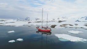 Segelbåtlopp i antenn för Antarktisisberghav arkivfilmer
