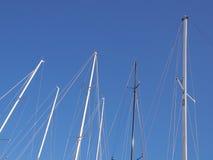 Segelbåtmaster mot den blåa himlen Arkivfoto