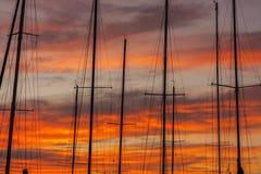 Segelbåtmaster och färgrik solnedgång Royaltyfri Bild