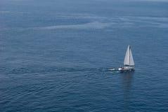 Segelbåtsegling i det ändlösa blått- och tystnadhavet arkivfoto