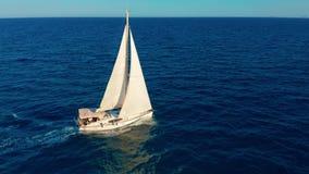 Segelb?t i hav Vit segla yacht i mitt av det gränslösa havet flyg- sikt arkivfilmer