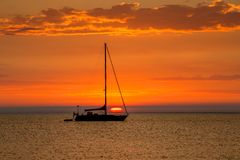 Segelboot am Anker mit schönem Sonnenuntergang im Hintergrund lizenzfreies stockbild