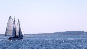 Segelboot auf blauem glänzendem Meer unter Sonnenschein Stockfotos