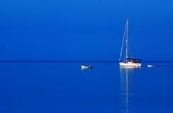 Segelboot auf blauem Wasser Stockfotos