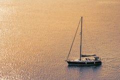 Segelboot auf dem Ozean mit Sonnenuntergang für einen Konzepthintergrund Lizenzfreie Stockfotos