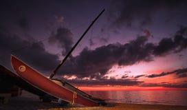 Segelboot auf den Strand gesetzt bei Sonnenuntergang lizenzfreie stockfotografie