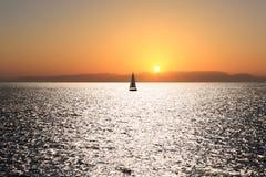 Segelboot auf einem Sonnenuntergang Stockbilder