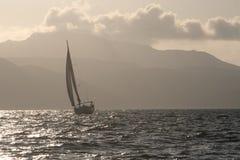 Segelboot auf einem stürmischen Meer gegen das felsige Ufer stockfotografie