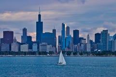 Segelboot auf Michigansee mit Chicago-Skylinen im Hintergrund als Sonne fängt an einzustellen Stockfotos
