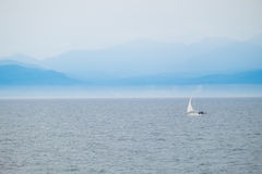 Segelboot auf Ozean mit nebelhafter Gebirgshintergrund Lizenzfreies Stockfoto