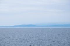 Segelboot auf Ozean mit nebelhafter Gebirgshintergrund Stockfotografie
