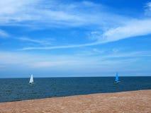 Segelboot blau und weiß mit Himmelblaumeer Lizenzfreie Stockbilder