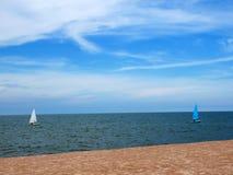 Segelboot blau und weiß mit Himmelblaumeer Stockbild