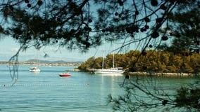 Segelboot, das auf das Meer schwimmt Küstenlinie im Hintergrund stock video