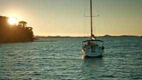 Segelboot, das auf das Meer während des Sonnenuntergangs schwimmt Küstenlinie im Hintergrund stock video footage