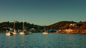 Segelboot, das auf das Meer während des Sonnenuntergangs schwimmt Küstenlinie im Hintergrund stock video