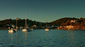 Segelboot, das auf das Meer während des Sonnenuntergangs schwimmt Küstenlinie im Hintergrund stock footage