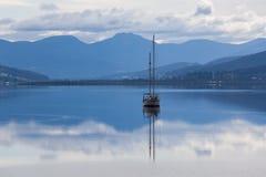 Segelboot, das im ruhigen Wasser von Huon River, Tasmanien sich reflektiert Lizenzfreie Stockbilder