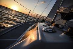 Segelboot in der hohen See bei Sonnenuntergang Lizenzfreies Stockbild