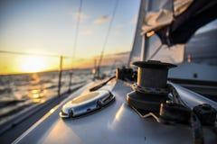 Segelboot in der hohen See bei Sonnenuntergang Lizenzfreie Stockfotos