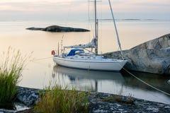 Segelboot festgemachte lange Seite eine kleine Felseninsel Lizenzfreie Stockfotografie