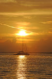 Segelboot im Ozean mit Sonnenuntergang Lizenzfreies Stockbild