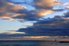 Segelboot im Ozean und im Sonnenuntergang lizenzfreie stockbilder