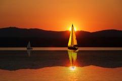 Segelboot im Sonnenuntergang Stockfotos