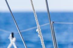 Segelboot-Leichentücher und Seile mit unscharfem See-und Himmel-Hintergrund Lizenzfreies Stockbild