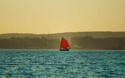 Segelboot mit den roten Segeln, die in den See schwimmen Stockfotografie