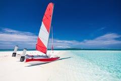 Segelboot mit rotem Segel auf einem Strand von verlassenem tropischem islan Stockbild
