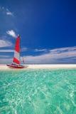 Segelboot mit rotem Segel auf Strand von Tropeninsel Lizenzfreie Stockfotos