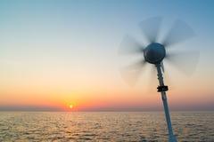 Segelboot mit Windkraftanlagesegeln auf Nordsee bei Sonnenuntergang, Nethe lizenzfreie stockfotografie