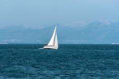 Segelboot schwimmt schnell gegen die entfernten Berge Lizenzfreies Stockbild