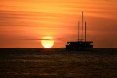 Segelboot silhouettiert bei Sonnenuntergang Stockbild