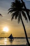 Segelboot und Schattenbild von Leuten gegen einen schönen Sonnenuntergang Lizenzfreie Stockfotos