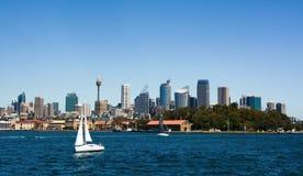 Segelboot, welches das tiefe blaue Wasser von Sydney Harbor gegen einen Hintergrund der Stadtskyline kreuzt Lizenzfreie Stockfotografie