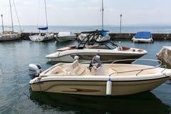 Segelboote und Fischerboote in Lazise auf dem Garda See Stockbilder