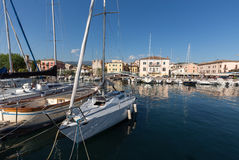 Segelboote und Fischerboote in Porto di Bardolino beherbergten auf dem Garda See Lizenzfreie Stockbilder
