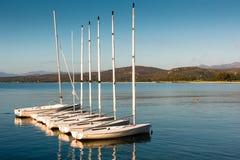 Segelboote verankerten nahe Strand auf ruhigem See stockfotos