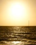 Segelbootschattenbild gegen drastischen goldenen Sonnenuntergang über dem Meer Lizenzfreie Stockbilder