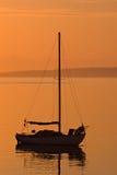 Segelbootschattenbild während des orange Sonnenaufgangs Stockbild