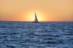 Segeljacht im Meer bei Sonnenuntergang Stockbild