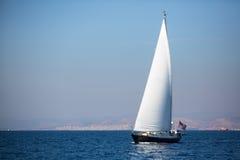 Segeljacht mit weißen Segeln im Nebel im Meer nahe dem Küste Luxus Lizenzfreie Stockfotos